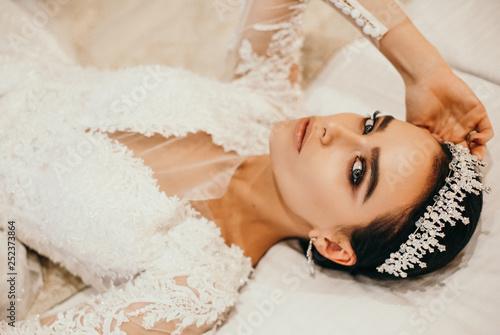 Obraz na płótnie beautiful sensual bride with dark hair in luxurious wedding dress and accessorie