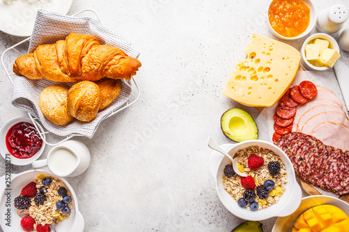 Continental breakfast table with croissants, jam, ham, cheese,  butter, granola and fruit, copy space Fototapet