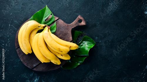 Fotografia Fresh yellow bananas on a black stone table