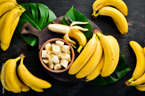 Fotomural Bananas on a black wooden surface