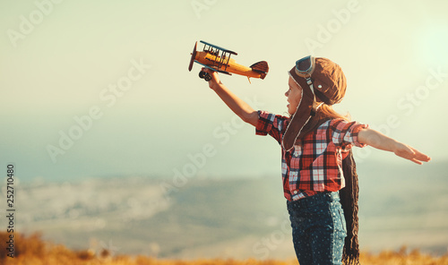 Fotografija Child pilot aviator with airplane dreams of traveling in summer  at sunset