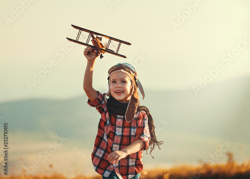 Canvastavla Child pilot aviator with airplane dreams of traveling in summer  at sunset