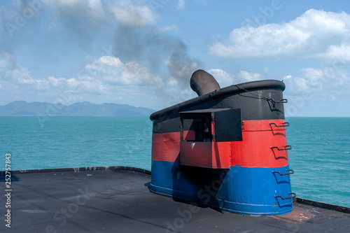 Fototapeta Smoke from ferry boat flue during sea with sunlight, sea water and clear sky in