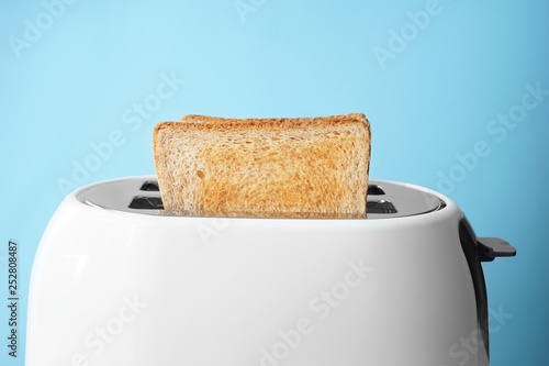 Slices of bread with toaster on color background Fotobehang