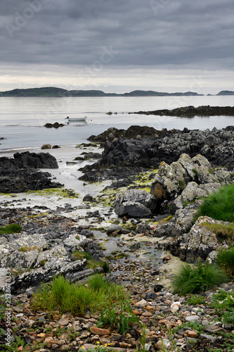 Sand beach and rocky shore and clouds on Isle of Iona with boat on Sound of Iona Fototapeta