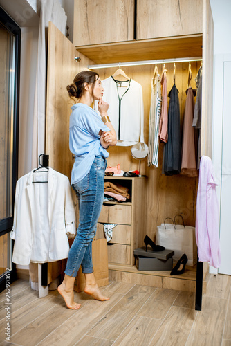 Fotografia Young woman choosing clothes to wear, standing in the wardrobe at home