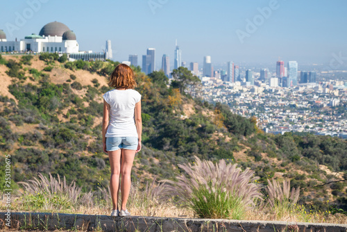 Fotografia, Obraz Young woman is looking at the city of Los Angeles, California, USA from Griffith Park