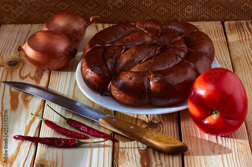 Vászonkép Preparation of a festive table, on a table of smoked sausage, a tomato, onions and acute red pepper to improve apetit
