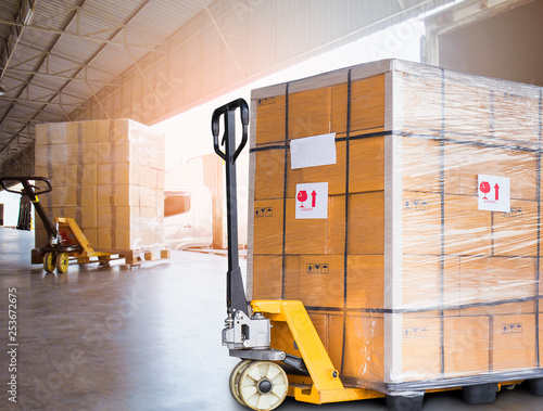 Stampa su Tela Large shipments goods and hand pallet truck at interior warehouse dock