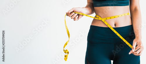 Canvas Close up shot of woman with slim body measuring her waistline and torso