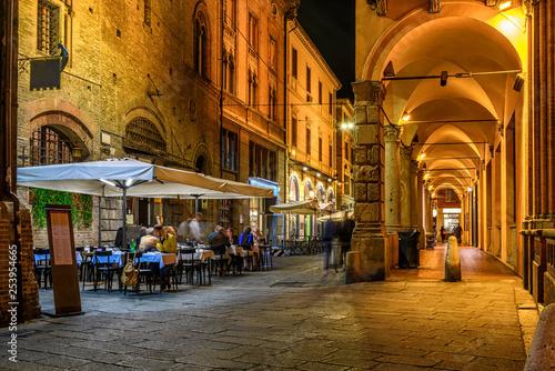 Photo Old narrow street with arcade in Bologna, Emilia Romagna, Italy