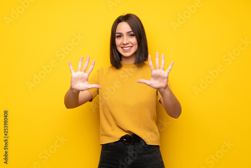 Leinwand Poster Young woman over yellow wall counting ten with fingers