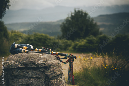 Canvas Print isolated bagpipes in scotland highlands laying on a rock in middle of summer gre