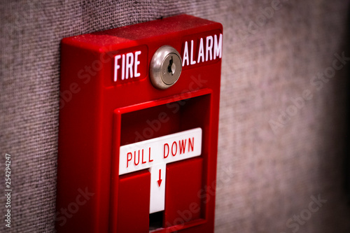 """Manual fire alarm activation pull station on wall - signage reading: """"FIRE ALARM"""" and """"PULL DOWN"""" Fototapeta"""