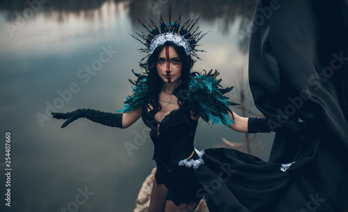 Fotografia A woman in the image of a fairy and a sorceress standing over a lake in a black dress and a crown