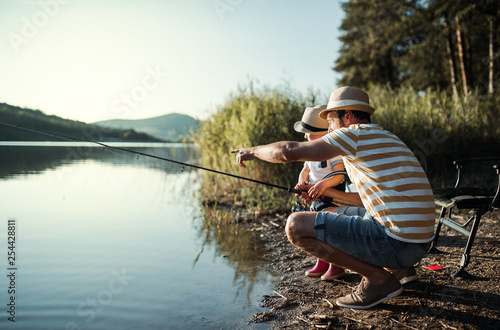 Fotografija A mature father with a small toddler son outdoors fishing by a lake