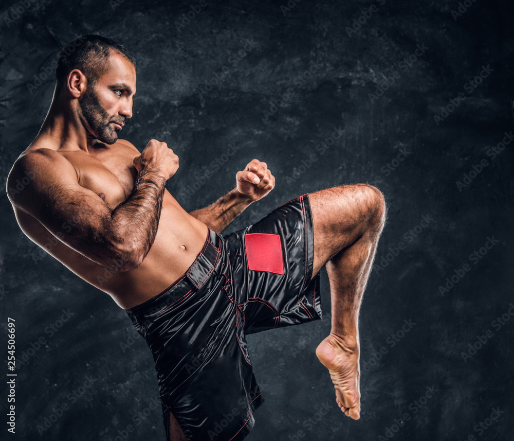 Professional Muay Thai boxer showing kick fighting technique. Studio photo against a dark textured wall