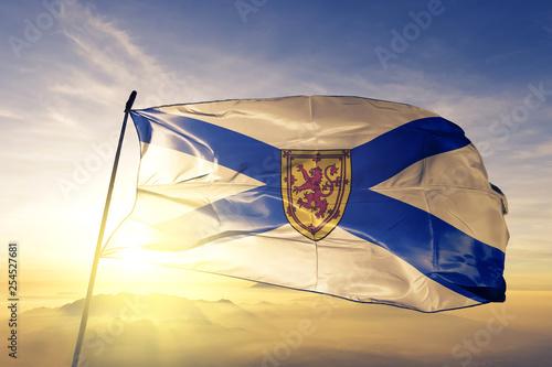 Obraz na płótnie Nova Scotia province of Canada flag waving on the top sunrise mist fog