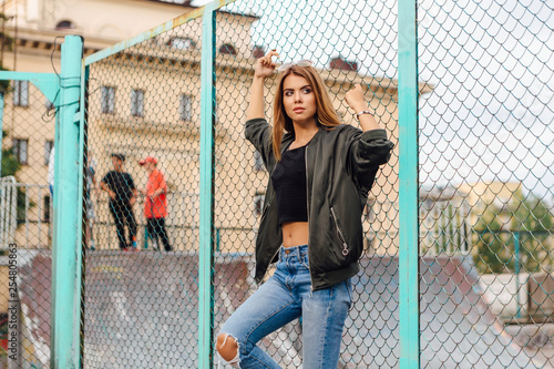 Fotografia Fashion portrait of trendy young woman wearing sunglasses, and bomber jacket sit
