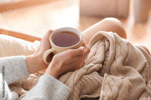 Fotografie, Obraz Young woman drinking hot tea at home, closeup