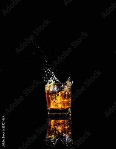 Photo Isolated shot of whiskey with splash on black background