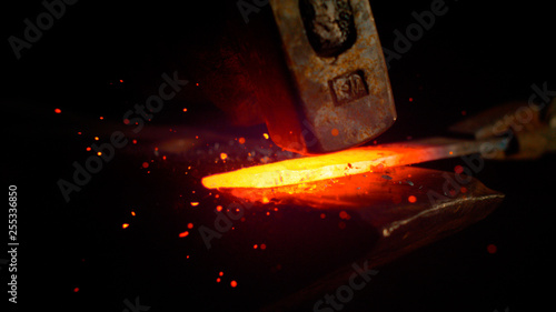 Fotografia MACRO: Red hot piece of metal is held by tongs and struck by a big hammer
