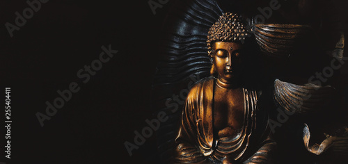 Leinwand Poster Golden Gautama Buddha statue with a black background.