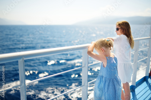 Canvas Print Adorable young girls enjoying ferry ride staring at the deep blue sea