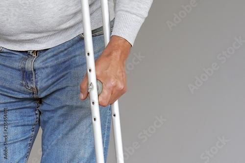 Fotografija Man on crutches on a gray background
