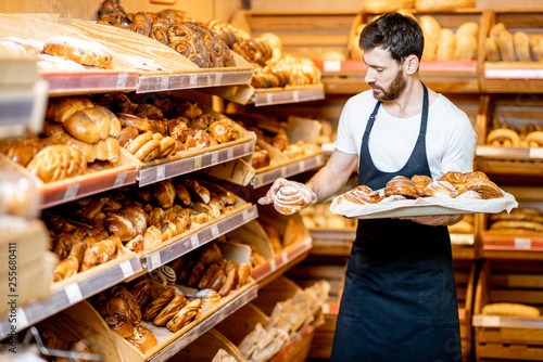 Handsome baker in uniform putting fresh pastries on the shelves in the supermark Poster Mural XXL