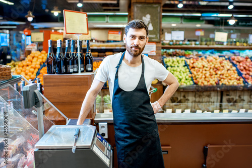 Obraz na plátně Portrait of a handsome seller or shop worker in apron standing at the counter in