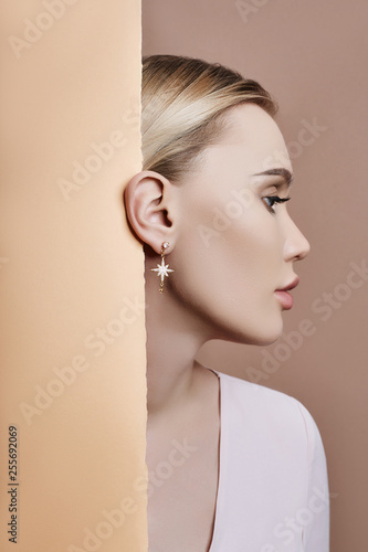 Leinwand Poster Earrings and jewelry in ear of a sexy blonde woman pressed against the paper beige