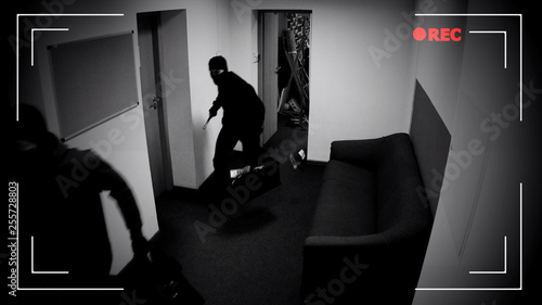 Photo Masked thieves running off with bags of money, shooting in surveillance camera