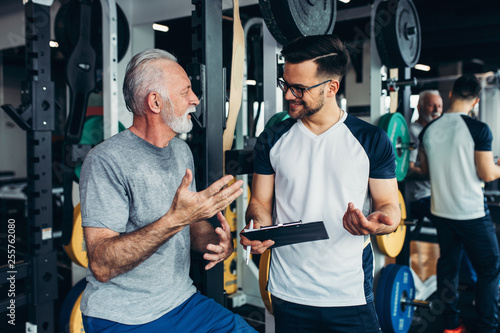 Senior man exercising in gym with his personal trainer. Fototapet