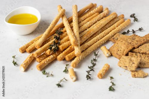 Fényképezés Italian grissini or salted bread sticks and multigrain crackers on a light stone background