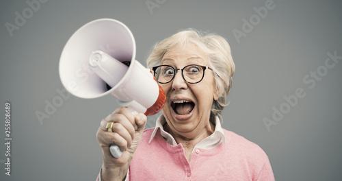 Vászonkép Cheerful senior lady shouting into a megaphone