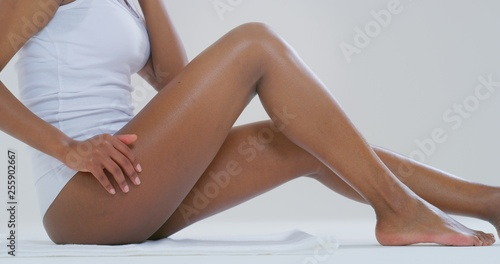 Fotografía Close up of young dark skin woman with perfect body touching gently her hairless soft and silky legs after depilation isolated on a white background