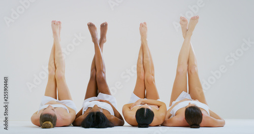 Fotografija Portrait of beautiful young women of different ethnicities with perfect firm and slim bodies with hairless soft and silky legs crossed isolated on a white background
