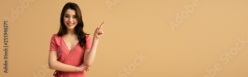 Valokuva panoramic shot of cheerful brunette woman pointing with finger while standing is