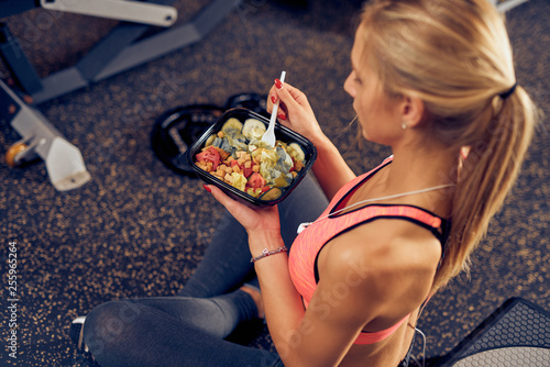 Photo Top view of woman eating healthy food while sitting in a gym