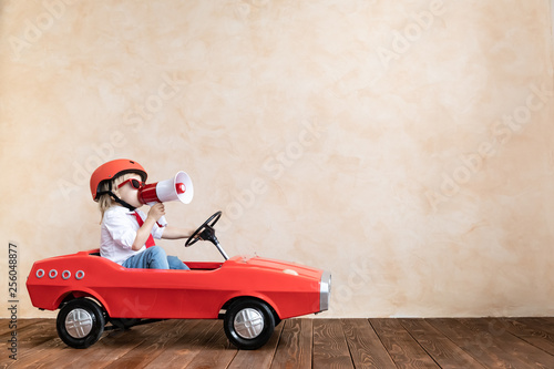 Funny kid driving toy car at home