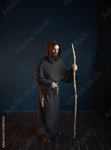 Fotografia, Obraz Medieval monk in robe with hood rests on a stick