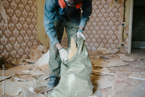 Fotografia Worker cleans the trash in the apartment in the bag