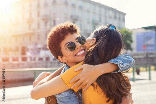 Two women hugging in town square Fototapet