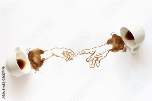Two espresso cups with hand drawing hand to hand. Helping hands, coffee art or creative concept. Top view