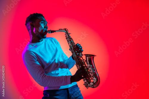 African American handsome jazz musician playing the saxophone in the studio on a neon background Fototapeta