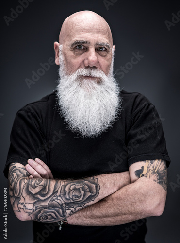 Wallpaper Mural studio portrait of a bald man with tattooed arms and white beard