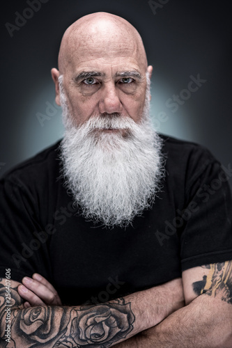 Photo studio portrait of a bald man with tattooed arms and white beard