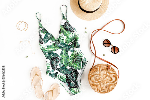 Photo Woman's beach accessories: swimsuit with tropical print, rattan bag, straw hat on white background