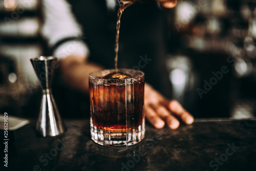 Stampa su Tela A close up shot of a bartender pouring whiskey